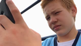 Boy sending text messages on his cell phone 4k