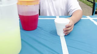 Boy serving red drink at refreshment stand
