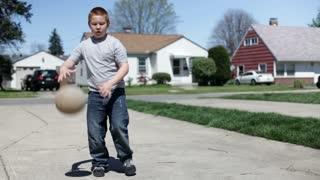 Boy shoots basketball in driveway