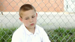 Boy sitting against fence looks at camera