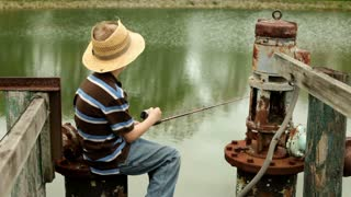 Boy sitting on Dock Fishing