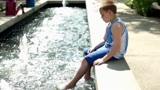Boy sitting on side of water kicking feet