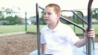 Boy sitting on stationary merry go round