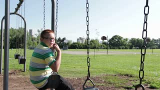 Boy sitting on swing steadicam shot