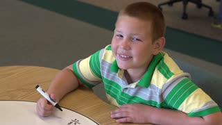 Boy smiles at camera then works math problem