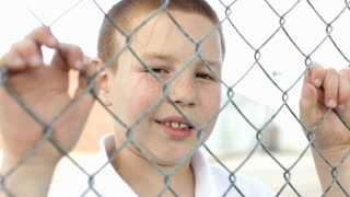 Boy smiling with hands on fence