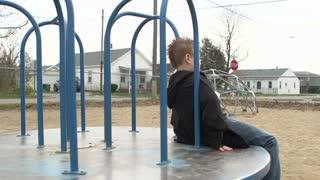 Boy spins by on merry go round