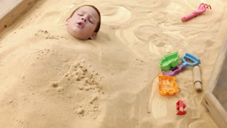 Boy stuck in sand box
