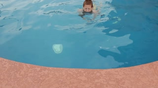 Boy swims underwater to edge of pool