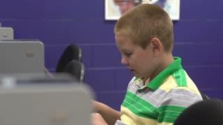Boy typing at keyboard in computer lab pan shot