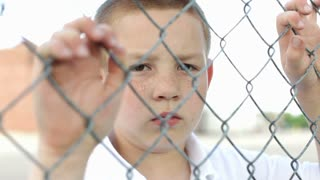 Boy with hands on fence looks at camera