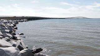 Bridge in distance over ocean water