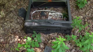 Broken tube television out in woods tilt shot 4k