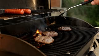 Burgers cooking on grill in hot sun