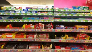 Candy aisle at the gas station with man purchasing snack 4k