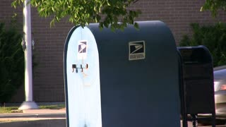 Car Dropping off Mail in Post Office box