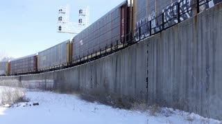 Cargo train driving by with snow on ground