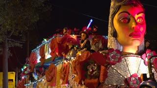 Carmen float Krewe throwing beads into crowd