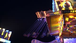 Carnival lights and swings flashing at night 4k