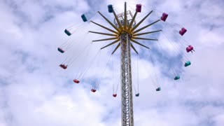 Carnival swings high in the blue sky going round 4k
