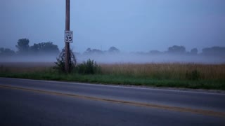 Cars driving by field with evening fog