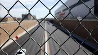 Cars driving by focused on chain link fence time lapse