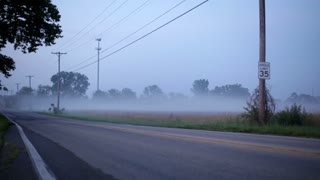 Cars driving by on foggy back road