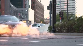 Cars driving by with steam coming from manhole