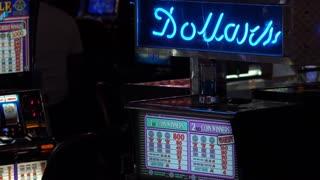 Casino slot machine with Dollars neon sign above it 4k