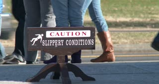 Caution Slippery Conditions sign with people walking by 4k