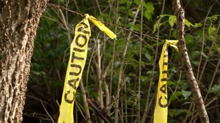Caution tape in woods at crime scene 4k