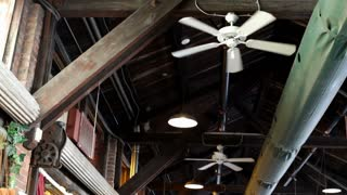 Ceiling of old building with fans spinning