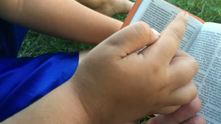 Child and adult reading through bible in grass.