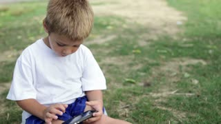 Child busy playing on cell phone in grass