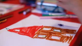 Child coloring in picture of house