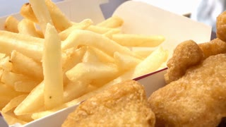 Child eating french fries with nuggets at fast food 4k