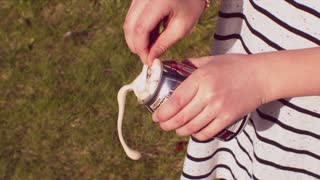 Child opening can of soda that sprays in slow motion