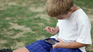 Child playing interested in cell phone outdoors