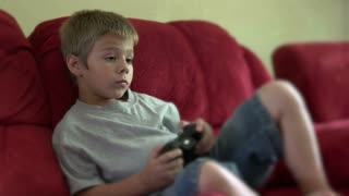 Child playing video game sitting on couch