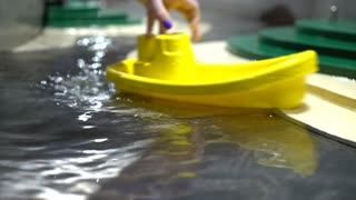 Child playing with toy boats in water playground 4k