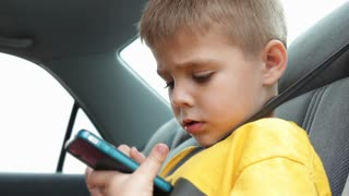 Child using smart phone in car