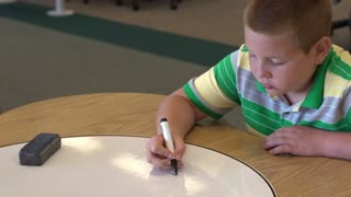 Child working math problem at table