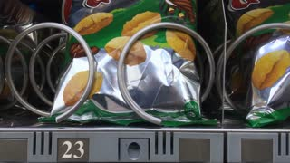 Chips coming out of vending machine in Valencia Spain 4k