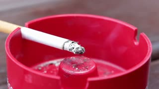 Cigarette in ashtray burning