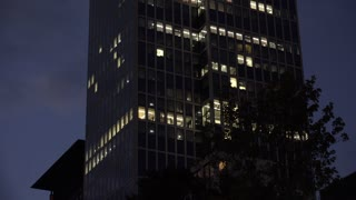 City office building with lights on at night 4k