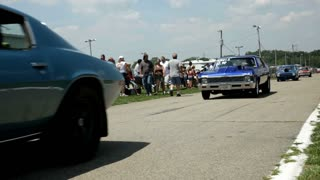 Classic Muscle cars driving down street