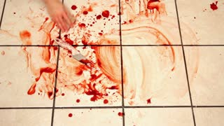 Cleaning blood from kitchen tile with knife laying