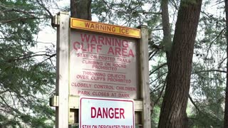 Cliff area warning in forest tilt shot