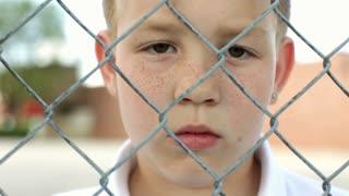 Close up of Upset Boy behind fence