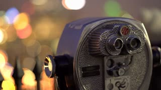 Coin operated binoculars in city at night 4k